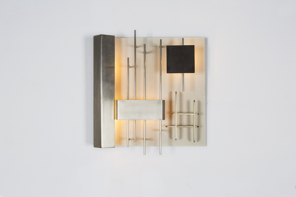 This wall sconce is by Gio Ponti, who was well known for his asymmetrical and organic shapes.