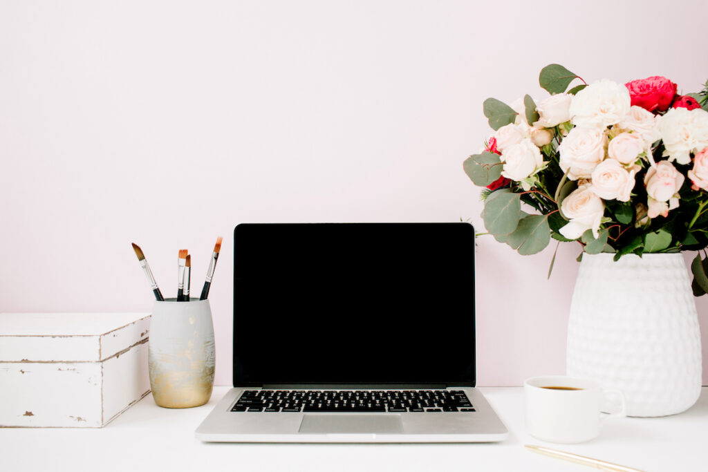 a laptop next to a vase of flowers - a computer is at the heart of everything we at adroyt do