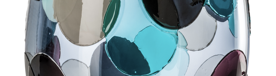 a glass vase with bright blue organically shaped circles on it