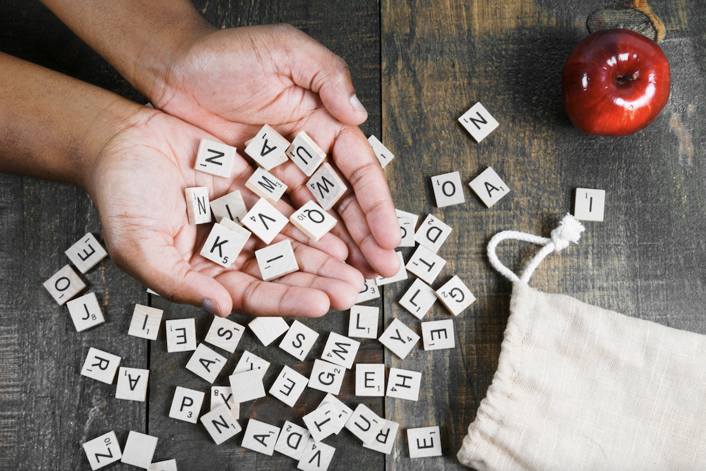 Scrabble letters scattered on a wooden table and held in a person's hands. Image by Nicole de Khors; courtesy Burst.